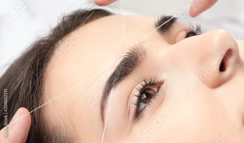 Canvas Print Young woman having professional eyebrow correction procedure in beauty salon, cl