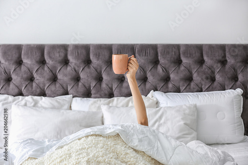 Woman with cup of coffee on bed at home