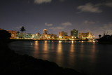 Looking Westwardly at the Boca Raton City Skyline from the Intracoastal Waterway at Camino Real and SR A1A at Night in a Long Time Exposure Creating Streaks of Car Headlights and Smooth Water