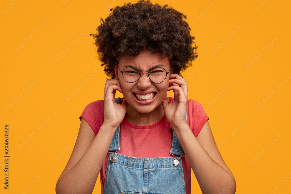 Fototapeta Portrait of annoyed frustrated American female plugs ears and clenches teeth, being irritated with annoying loud sound, isolated over yellow background. People, problems and emotions concept.