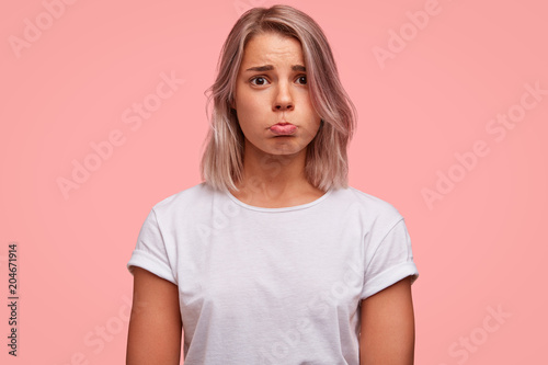 Tableau sur Toile Abused pretty female curves lower lip, being offended during quarrel, looks with sorrowful miserable expression, wears casual white t shirt, isolated over pink background