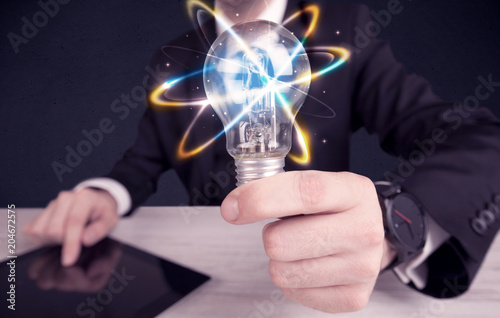 Papiers peints Secheresse A classy businessman holding a colorful light bulb with shining circles in front of dark background concept.