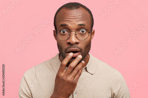 Close up shot of handsome stupefied young African American male stares surprisingly as reads strange headline in journal, isolated over pink background. Black hipster male realizes hoax or fraud