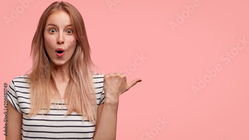 Fotografía  Horizontal portrait of amazed lovely female looks with terrified expression, has