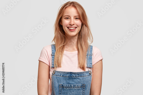Fotografía  Portrait of attractive female with pleasant appearance, charming smile, wears casual denim overalls, being in good mood after stroll with in company of best friend