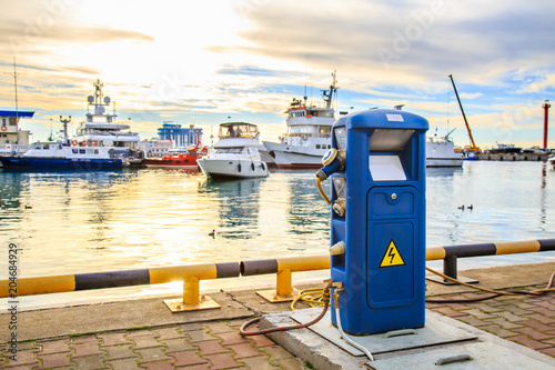 Charging station for boats, electrical outlets to charge ships in harbor - supply electricity for recharging of battery on shore in marina jetty. Luxury yachts docked in port at sunset.