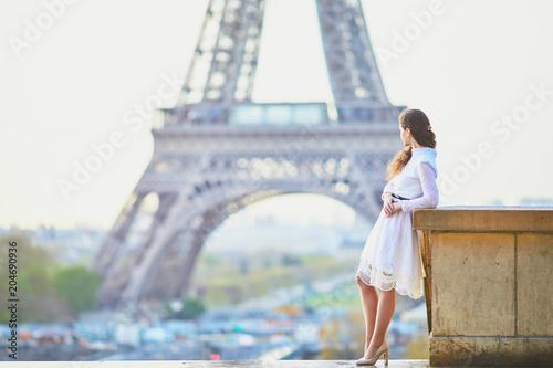 фотография Woman in white dress near the Eiffel tower in Paris, France