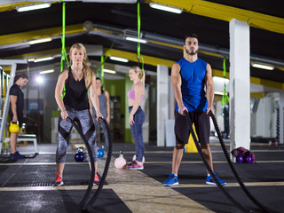 sports couple doing battle ropes crossfitness exercise