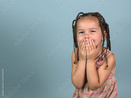 Fotografie, Obraz  Adorable girl with hands over mouth on blue background with room for copy