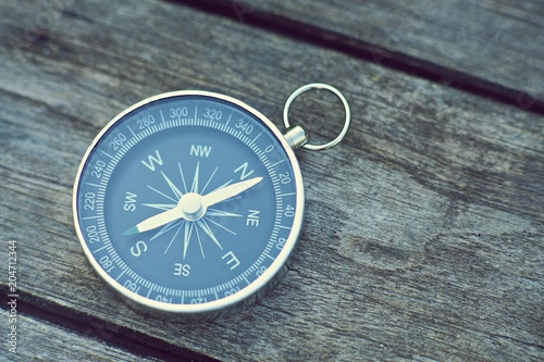 Compass on old wooden table background, journey concept, vintage tone