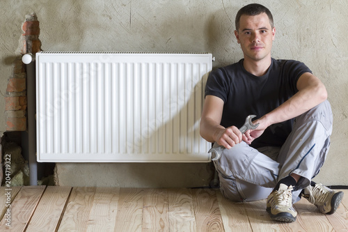 Young handsome plumber sitting on floor with wrench in hand near successfully installed heating radiator in empty room of a newly built apartment or house. Construction, maintenance and repair concept