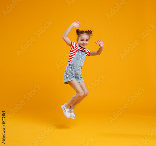 Keuken foto achterwand Restaurant funny child girl jumping on colored yellow background