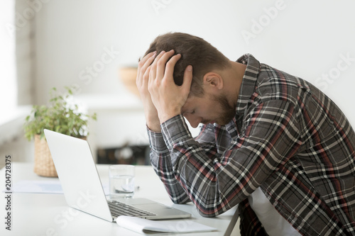 Fotografía Frustrated depressed man holding head in hands shocked by bankruptcy stock downf