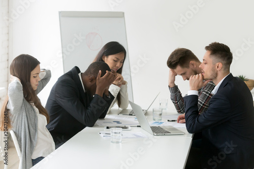 Stressed multiracial team thinking of problem solution at emergency office meeti Fotobehang