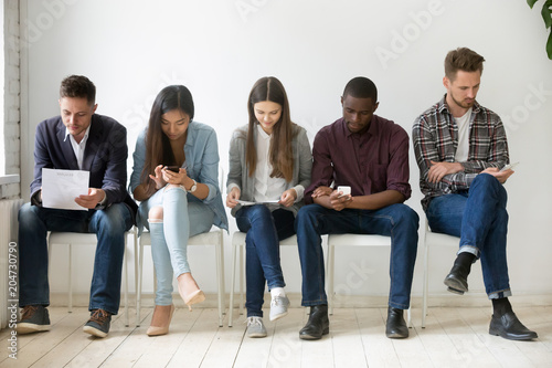 Multi-ethnic millennial people holding phones and resumes