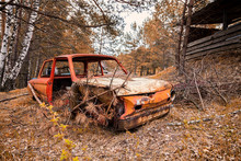 Close-up Of An Old Rusty Car With A Broken Door And No Wheels On The Background Of A Green Coniferous Forest