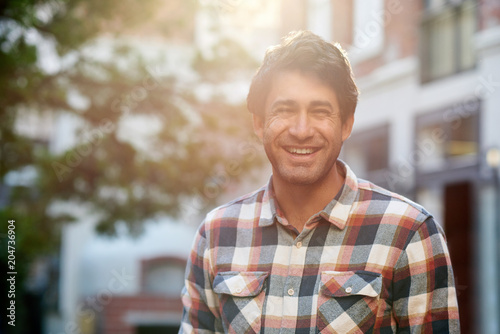 Smiling young man standing on a city street in summer