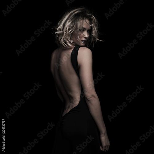 Fotografie, Tablou side view of beautiful blonde woman wearing black backless dress