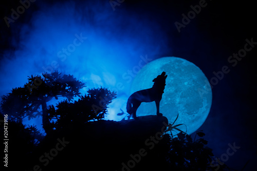 Naklejki wilk  silhouette-of-howling-wolf-against-dark-toned-foggy-background-and-full-moon-or-wolf-in-silhouette-howling-to-the-full-moon-halloween-horror-concept