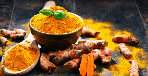 Foto op Plexiglas Kruiderij Composition with bowl of turmeric powder on wooden table