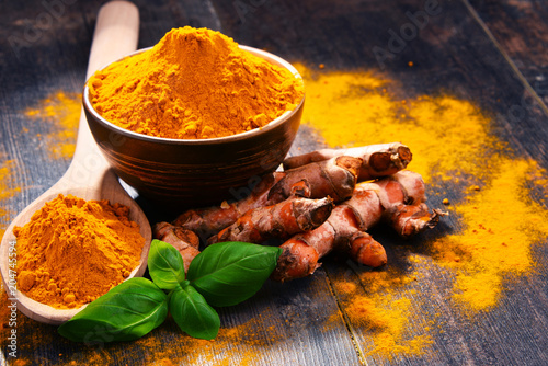 Tuinposter Kruiderij Composition with bowl of turmeric powder on wooden table