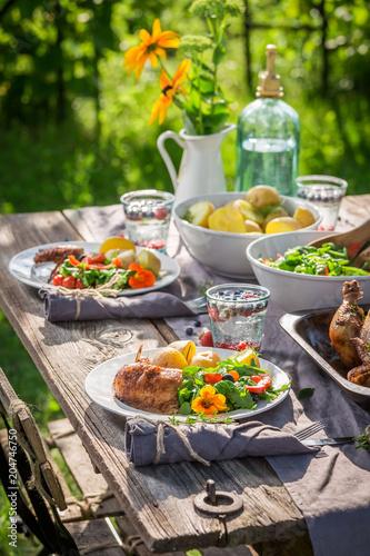 Dinner with chicken and vegetables served in summer garden