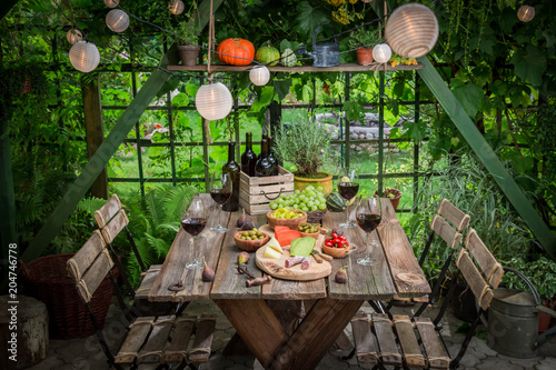 Fotobehang Tuin Preparation for dinner with wine and fruits in summer garden