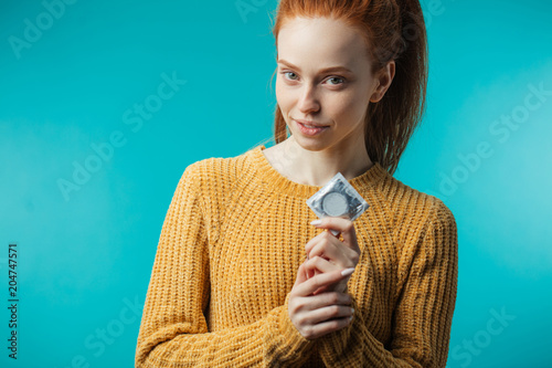 Cuadros en Lienzo Young redhaired woman showing condom in her hand , displaying her choice of safe pleasure and protection