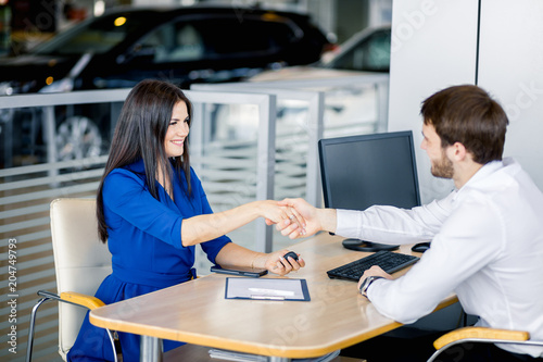 Fototapety, obrazy: Female buyer receiving congrats for closing successful deal, shaking hands with sales Manager