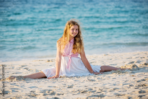 Foto op Aluminium Gymnastiek Cute young girl doing split at the beach