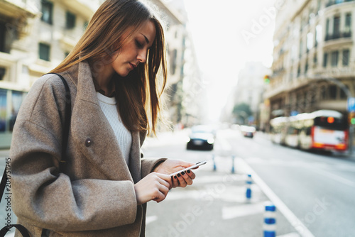Successful freelancer typing email on  mobile phone connected to wifi while walking the street. Charming hipster girl wearing stylish clothes searching needed address in the internet on a smartphone.