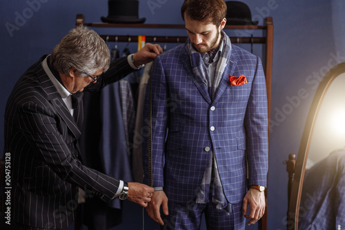 Mature professional Tailor taking measurements for sewing suit at tailors shop. Man with measuring tape busy. Client with beard and strict face tailor working. Exclusive Custom Made Cloth Concept.