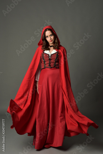 full length portrait of woman wearing red fantasy costume with cloak, standing pose on grey studio background. Fotomurales