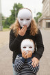 Girl and boy with a white mask with surprise gesture