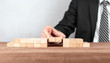 Close up of hand of businessman assembling a bridge made from little blocks.