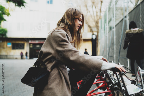 Foto op Plexiglas New York TAXI Stylish student girl in stylish clothes sitting on a rented city bicycle and ready to ride on. Freelancer female renting the bike to explore the city. Young tourist girl choosing bike to ride around