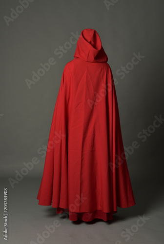 Obraz full length portrait of woman wearing red fantasy costume with cloak, standing pose on grey studio background. - fototapety do salonu