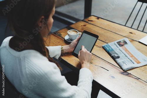 View from back photo of young caucasian female surfing the web on a digital tablet while sitting with a morning coffee cup and newspaper at the wooden table in a coffee shop. Woman reading news online