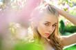 canvas print picture - Spring bloom concept. Lady in park on spring day. Girl on dreamy face, tender blonde near violet flowers of judas tree, nature background. Young woman enjoy flowers in garden, defocused, close up.