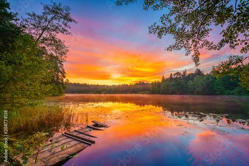 Foto op Aluminium Nachtblauw Bright sunrise over forest lake