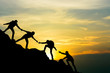 canvas print picture Group of people on peak mountain climbing helping team work with sunset background , travel trekking success business concept