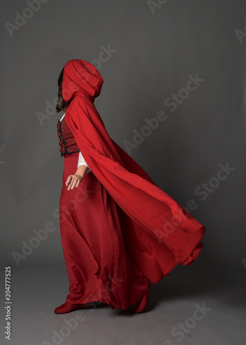 Fotografie, Obraz  full length portrait of woman wearing red fantasy costume with cloak, standing pose on grey studio background
