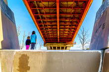 Two Girls In Awe Of The Massive Steel And Concrete Structure Of Mission Bridge Over The Fraser River On Highway 11 Between Abbotsford And Mission In British Columbia, Canada