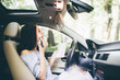 Modern smiling girl in car talk on phone and make-up on mirror