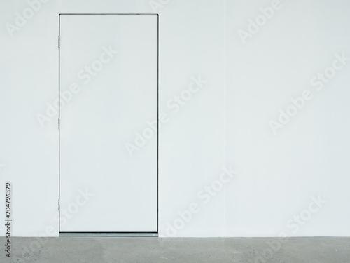 Fototapeta A closed white door on the white wall. obraz na płótnie