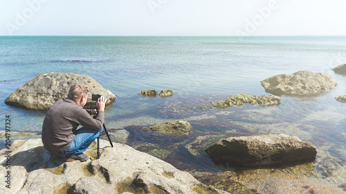 Foto op Aluminium Strand Man takes picture on the phone mounted on a tripod on a sea rocky coast