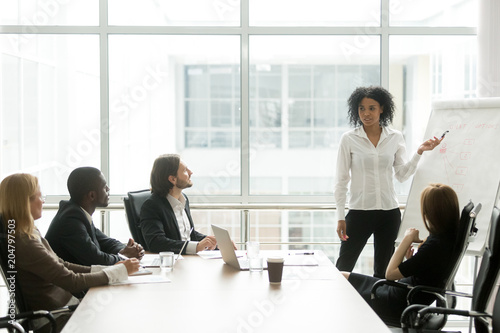 Obraz African american businesswoman giving presentation to executive team in meeting room, black business coach or employee working with flipchart reporting about work result, explaining new project idea - fototapety do salonu