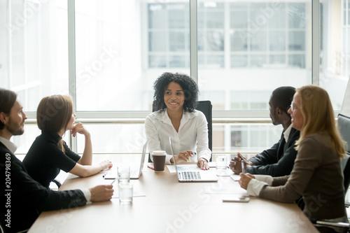 Pinturas sobre lienzo  Smiling friendly african female boss leading corporate diverse team meeting talk