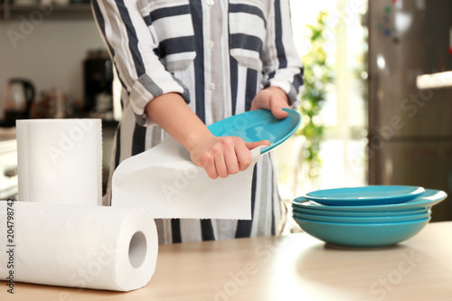 Fotografía  Woman wiping ceramic plate with paper towel indoors