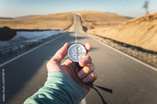 Foto  Compass in Hand mountain road background .Vintage Tone